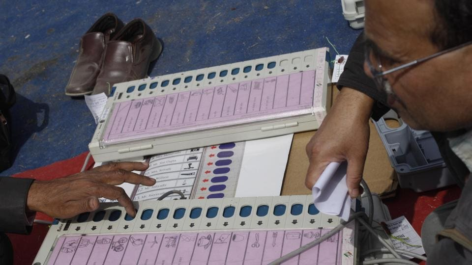 Polling officers check electronic voting machines (EVM) at an EVM distribution centre in Phase 2, Noida.