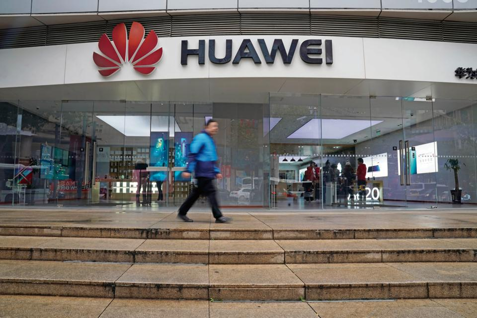 A man walks by a Huawei logo at a shopping mall in Shanghai, China December 6, 2018. REUTERS/Aly Song - RC12F87513A0