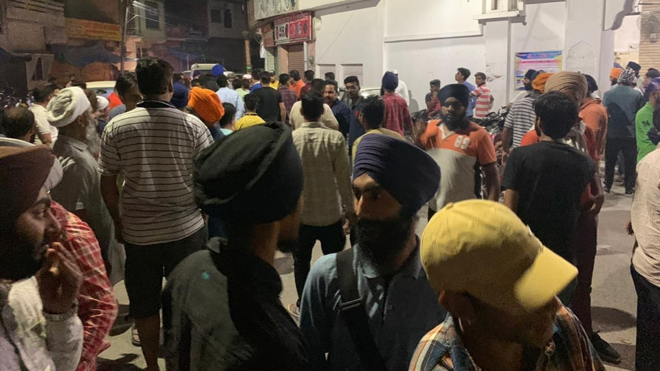 A mob gathers outside a gurudwara in Rudrapur in Uttarakhand after the police's  efforts to stop a Sikh truck driver in a no-entry zone escalated into violence.