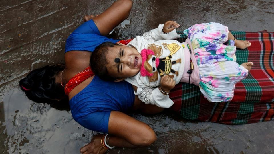 An infant lies on the back of a woman as she performs a ritual while worshipping Sheetala Mata, the Hindu goddess of smallpox, during Sheetala Puja, in Kolkata, West Bengal. (Rupak De Chowdhuri / REUTERS)