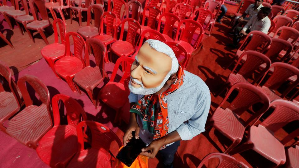 A supporter of the ruling Bharatiya Janata Party (BJP) wearing a mask of Prime Minister Narendra Modi checks his mobile phone as he attends an election campaign rally being addressed by Modi in Meerut in Uttar Pradesh. (Adnan Abidi / REUTERS)