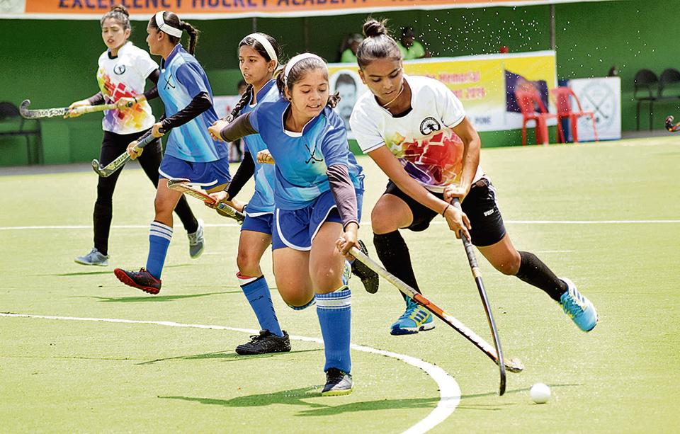 Super XI Girls Academy (blue) in action against Excellency Academy during the first edition of Moti John hockey tournament at Dhyan Chand hockey stadium on Saturday.