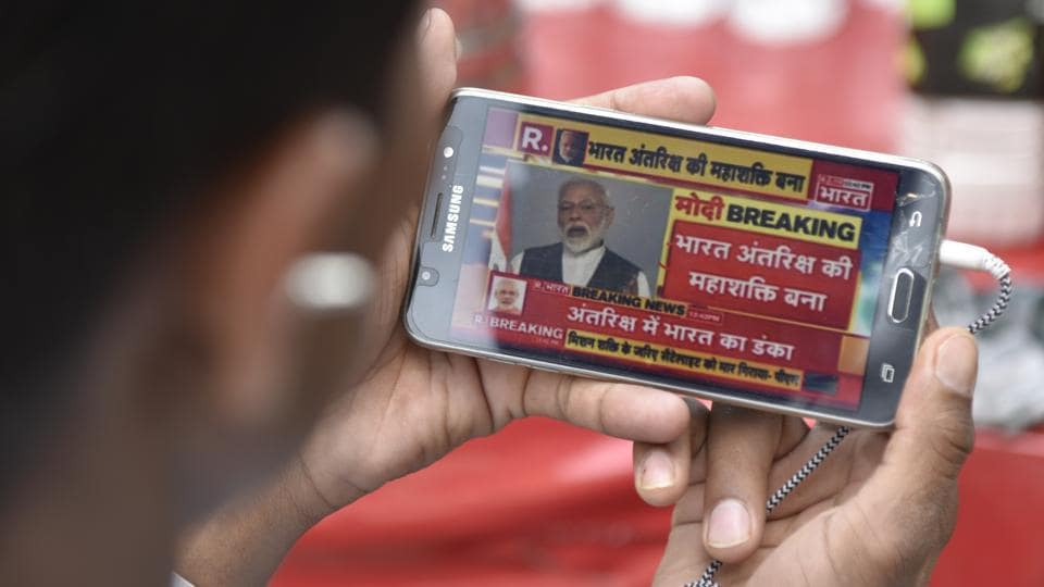 "A man watches Prime Minister Narendra Modi addressing the nation during his announcement of ""Mission Shakti"" on his smartphone, at Daryaganj, in Delhi. (Sanchit Khanna / HT Photo)"