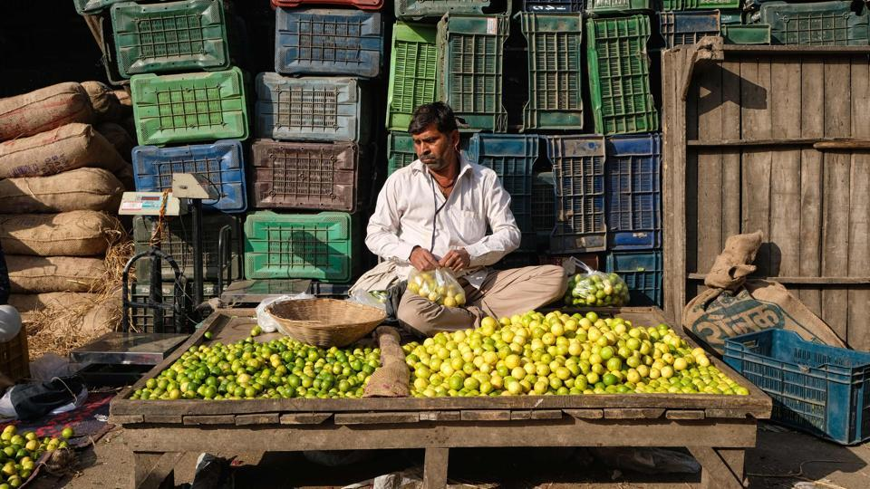 A vendor arranges lemons as he waits for customers at a fruit and vegetable wholesale market in New Delhi. (Noemi Cassanelli / AFP)