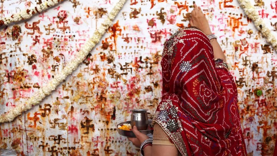 "A Hindu woman performs a ritual on the occasion of the ""Sheetala Saptami"" festival in Ajmer, Rajasthan, where women of the community pray for the well being of their family. (Himanshu Sharma / AFP)"