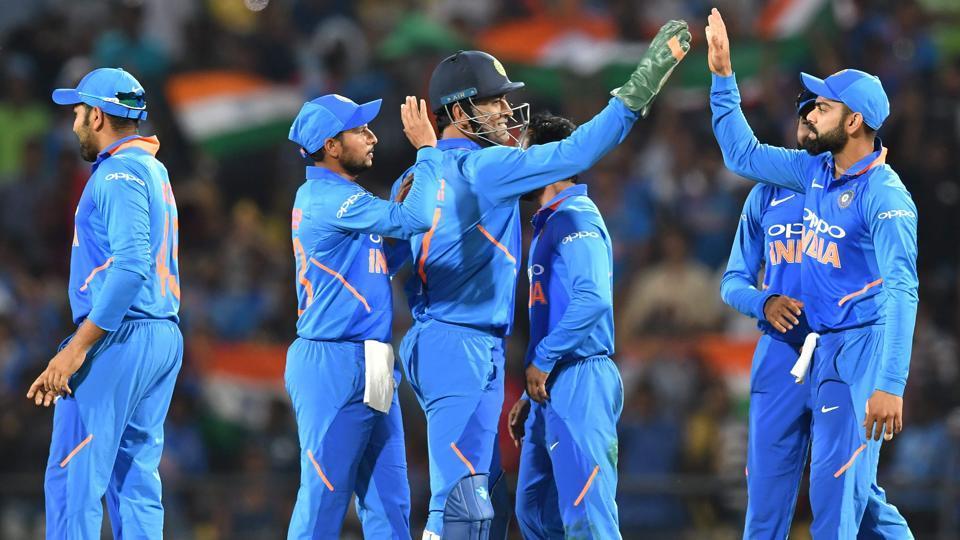 Virat Kohli (R) celebrates with Mahendra Singh Dhoni (C) and teammates.