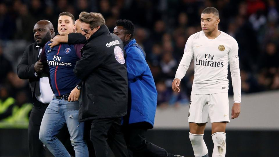 Paris St Germain's Kylian Mbappe looks on as a pitch invader is apprehended by stewards.