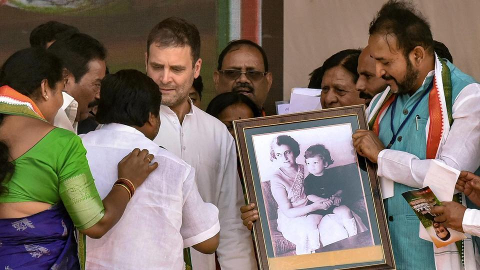 Congress party workers present a framed portrait of Indira Gandhi to Congress President Rahul Gandhi during a public rally at Zaheerabad,Telangana, on Monday.