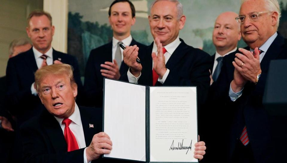 US President Donald Trump holds a proclamation recognizing Israel's sovereignty over the Golan Heights as he is applauded by Israel's Prime Minister Benjamin Netanyahu and others during a ceremony in the Diplomatic Reception Room at the White House in Washington, March 25, 2019