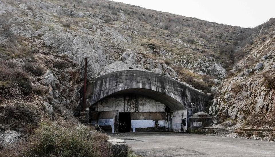 General view of the entrance of the main tunnel of the Gjader Air Base built near the city of Lezhe, on February 5, 2019. - On a barren hillside in northern Albania lies a portal to the country's communist past: a massive steel door creaks open to reveal a hidden former air base burrowed into the heart of the mountain. Made up of 600 metres (1,980 feet) of tunnels that once teemed with military life, the secret Gjader air base is now a depot for dozens of hulking communist-era MiG jets collecting dust in the darkness. Three decades after shedding communism, Albanian authorities are still trying to sell off the Soviet and Chinese-made aircraft, of which there are dozens more in another nearby air base.
