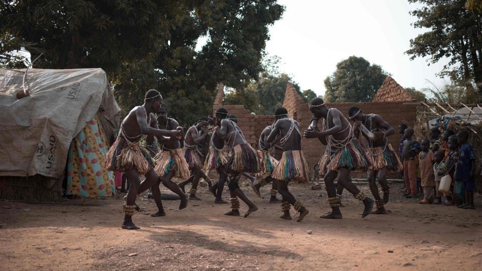 A group of Broto traditional musicians perform with bells made from palm leaves tied to their ankles in Bambari. Once ready, the musicians began their performance. Not long after a crowd approached, some sketched dance steps, happy to hear music rather than the rattle of gunfire. (Florent Vergenes / AFP)