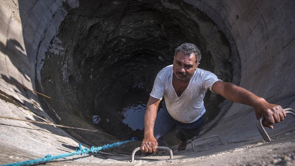 Sheikh Ishaque Ibrahim helps villagers fill buckets by climbing down the well. His task begins at 5 am and goes on for next four hours until the water dips further making it difficult to fill the buckets. In five districts, every village is reeling under drought, according to government figures. (Pratik Chorge / HT Photo)