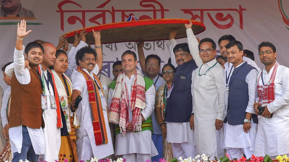 """Congress President Rahul Gandhi is felicitated with a traditional Assamese Japi (hat) during a public rally ahead of the Lok Sabha elections at Bokakhat, in Golaghat district, Assam. While addressing the rally Gandhi said, """"If voted to power, Congress will not allow Citizenship Amendment Bill. Congress will restore special status of northeastern states"""". (PTI)"""
