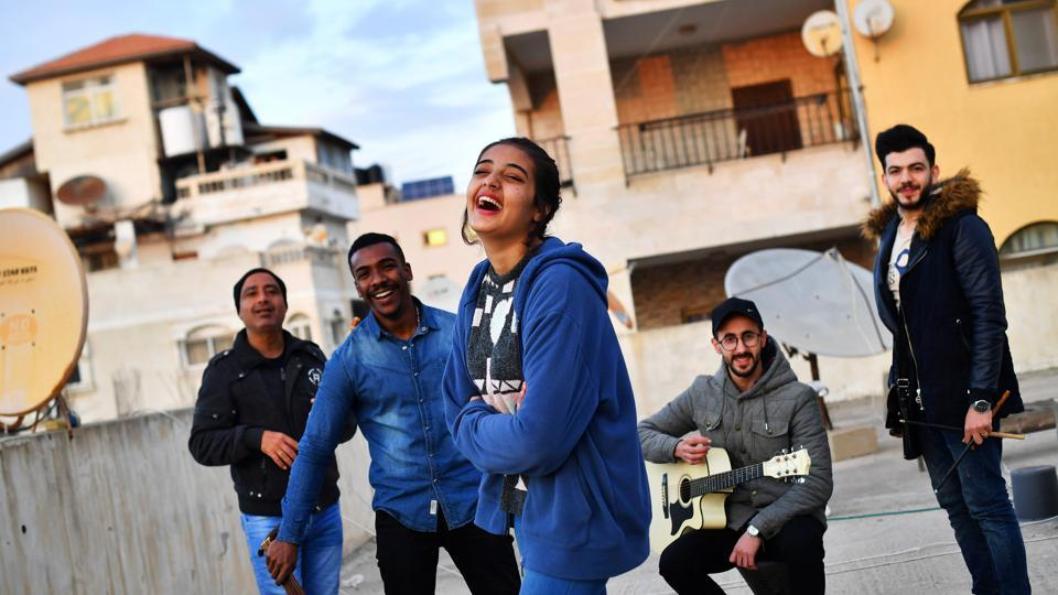 "Singer Rahaf Shamali, 15, Hamada Nasralla, 23, Ismaiel Al H'Razin, 42, Islam Mohsen, 24, and Saied Fadel of ""Solband"" pose on the roof of their apartment block in Gaza City. Martinez was warned many times by officials and bystanders on the street, in a more cautionary than menacing manner, not to photograph Hamas checkpoints and military installations. (Dylan Martinez / REUTERS)"