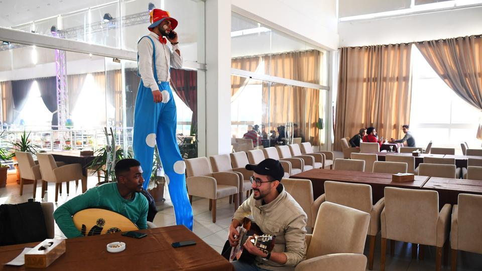 "Saied Fadel, 22, and Hamada Nasrallah, 23, of ""Solband"" rehearse, as a clown on stilts walks by. Solband were not allowed to play at their venue as the ruling Hamas government declined their permit to perform. Often, Martinez said he did not realise what the buildings were because their exteriors gave no sign of what might have been within.. (Dylan Martinez / REUTERS)"