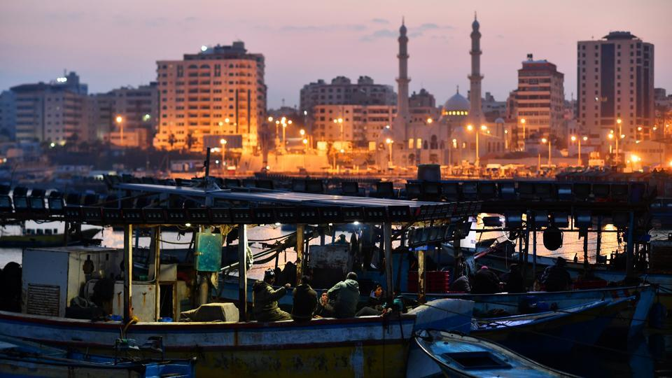 Street lights illuminate the Gaza skyline as the sun rises over fishermen as they bring their catch into the port in Gaza City. The mood had become more tense in recent weeks as the March 30 anniversary neared, with trails of Palestinian rockets and Israeli missiles again appearing in the skies above. (Dylan Martinez / REUTERS )