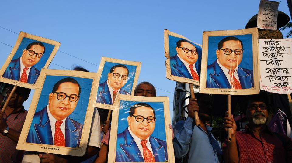Activists holds portraits of 20th century social reformer BR Ambedkar during a protest in Kolkata.