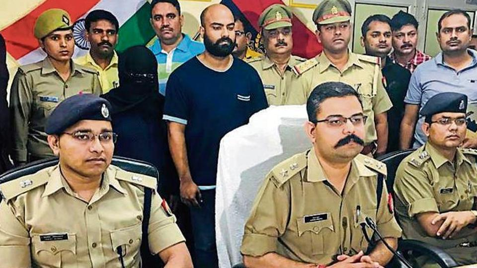 Police officers with the accused woman (face covered) and her husband, Noida.