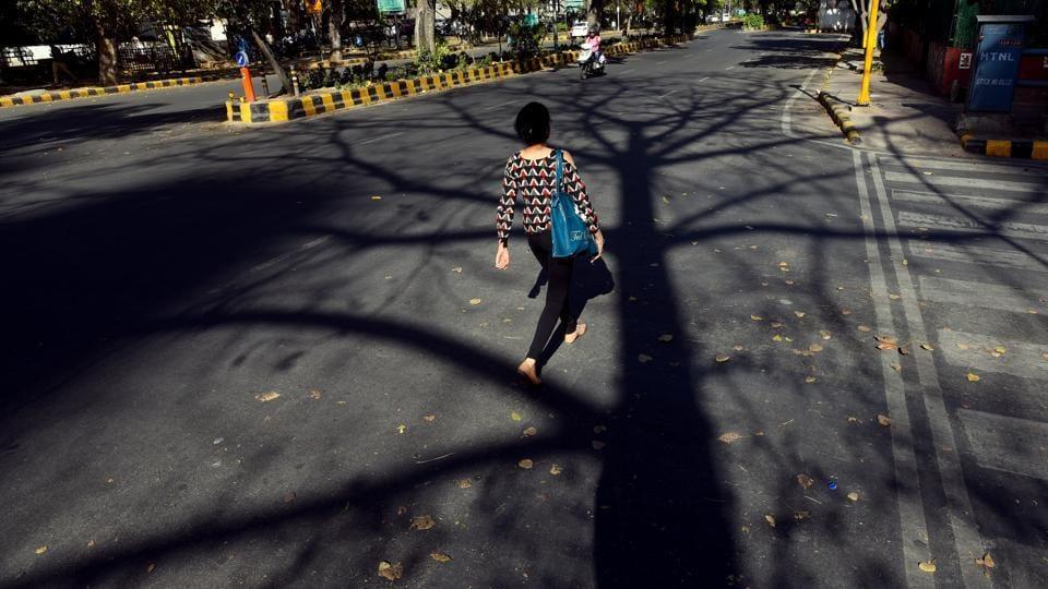 A pedestrian walks past autumn's doing at Janpath in New Delhi. (Amal KS / HT Photo)