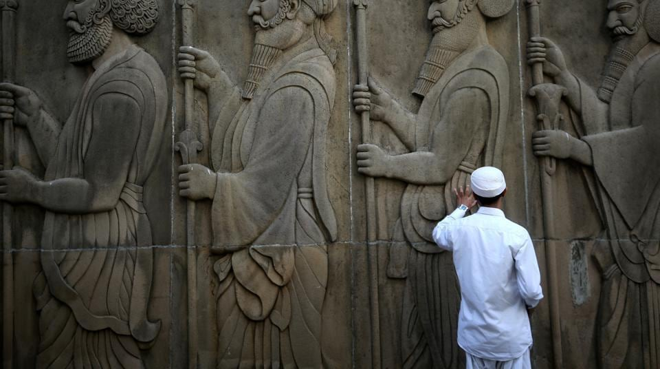 A man touches the wall of a Parsi fire temple. Anewsletter of the Parsi community has been banned by the Bombay Parsi Punchayet after it published reports on alleged corruption in property deals linked to the BPP.