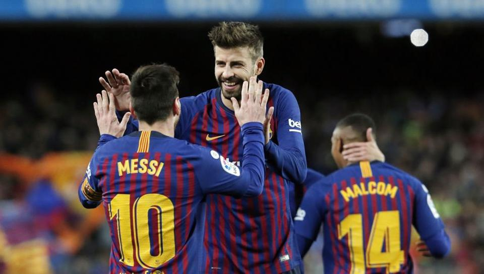 Barcelona's Argentinian forward Lionel Messi is congratulated for his goal by Barcelona's Spanish defender Gerard Pique (C) during the Spanish league football match between FC Barcelona and Club Atletico de Madrid