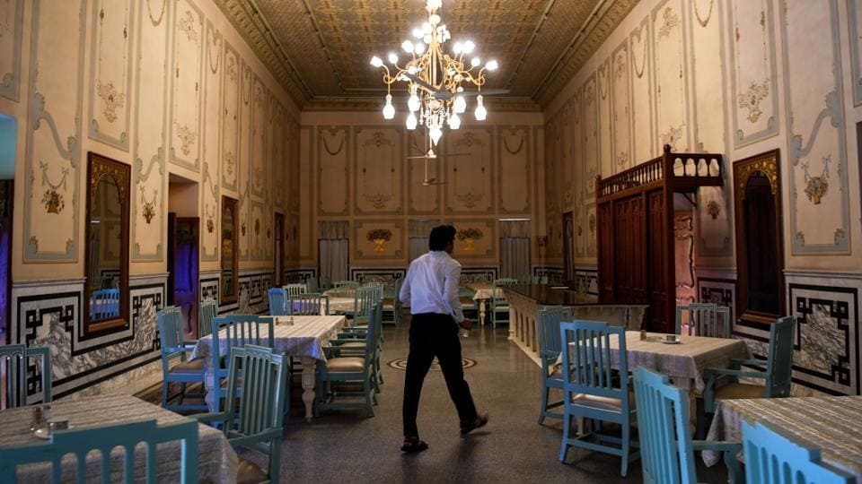 "A waiter walks inside the dining room of the Bhanwar Niwas. ""We opened our haveli for tourists as a way to better protect our heritage, and to let people live our ancestors' experience,"" Sunil Rampuria, whose family owns Bhanwar Niwas, one of the region's grandest and earliest havelis converted into a hotel, told AFP. (Chandan Khanna / AFP)"