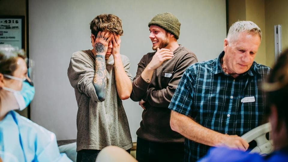 Elliott Dougherty and Matthew Eledge look on, along with Matthew's father Kirk , after Matthew's mother Cecile, gave birth to their daughter Uma in Omaha, on March 25, 2019. After testing to make sure that Cecile's body could tolerate the pregnancy, the embryo that would become Uma was implanted. (Ariel Panowicz / @arielpanowicz / REUTERS)