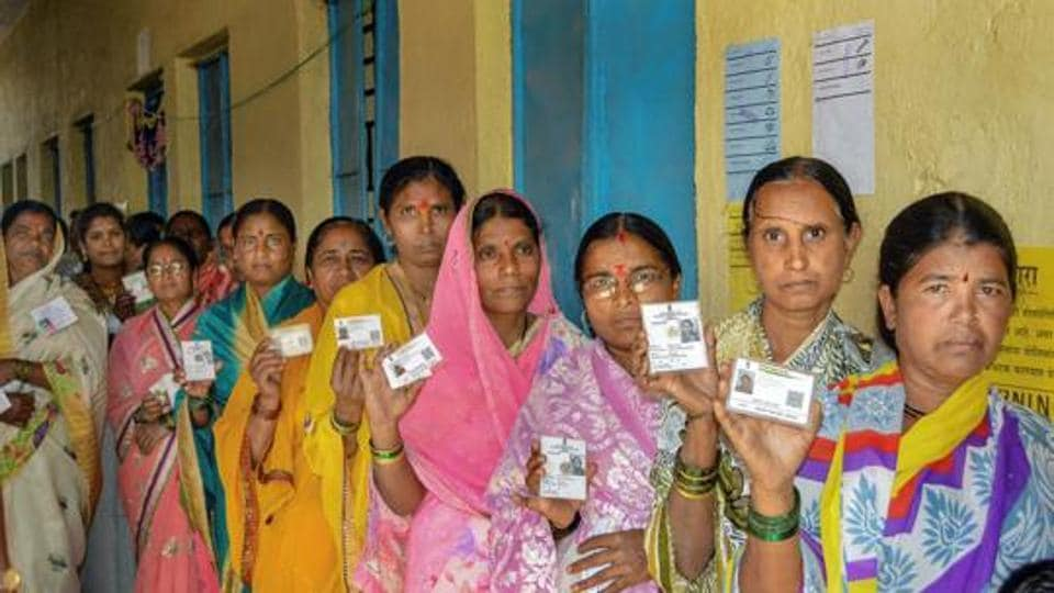 Karad: Voters show their identity cards as they stand in a queue at a polling station to cast their vote for the Gram Panchayat elections at Masur village, in Karad, Sunday, Feb. 24, 2019. (PTI Photo)(PTI2_24_2019_000044B)