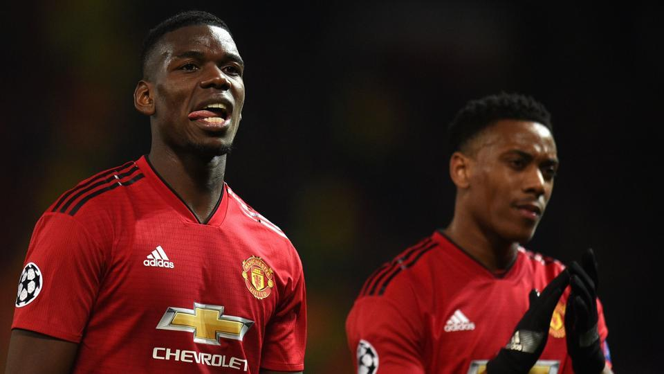 Manchester United's French midfielder Paul Pogba (L) and Manchester United's French forward Anthony Martial applaud fans.