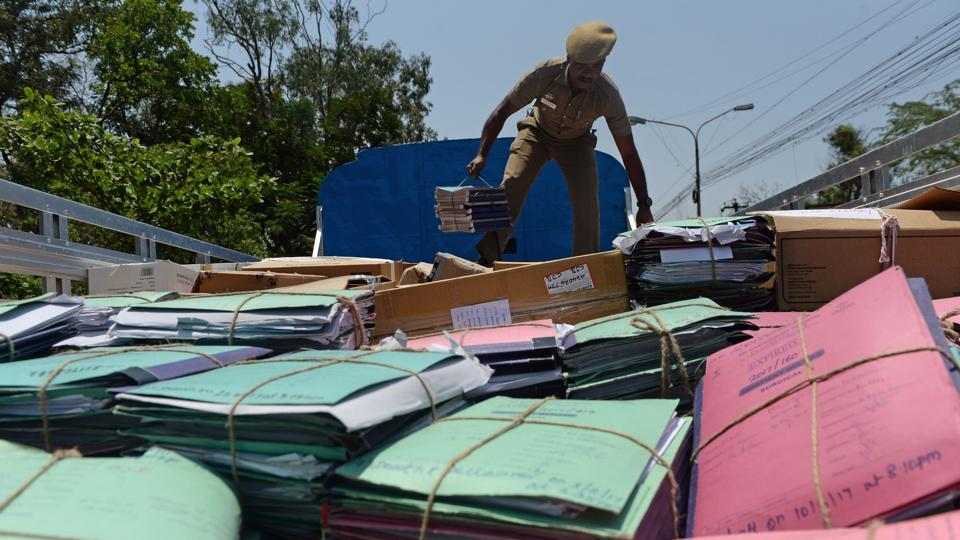 """A member of an election commission """"flying squad"""" searches a truck in Coimbatore, Tamil Nadu. It's a game of cat and mouse for Naresh and his flying squad, stopping vehicles to hunt for goodies being handed to voters in India's mammoth election that began yesterday. The illegal doling out of everything from alcohol to kitchen appliances has long been a feature of the vast undertaking that is Indian elections. But it's getting worse. (Arun Sankar / AFP)"""