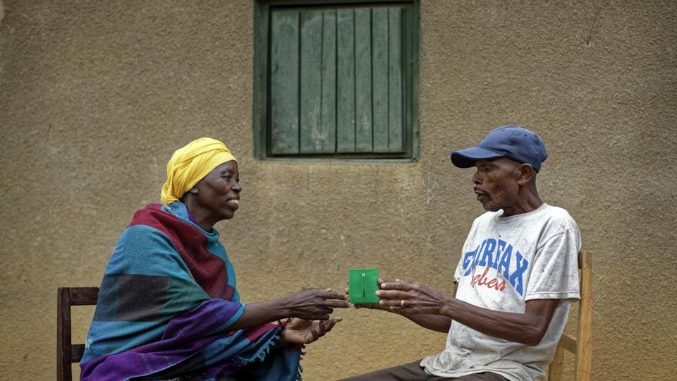 Genocide survivor Laurencia Mukalemera (L), a Tutsi, is offered a cup of water by Tasian Nkundiye (R), a Hutu who murdered her husband and spent eight years in prison for the killing and other crimes, before being interviewed at Nkundiye's home in the reconciliation village of Mbyo, near Nyamata, in Rwanda. (Ben Curtis / AP)