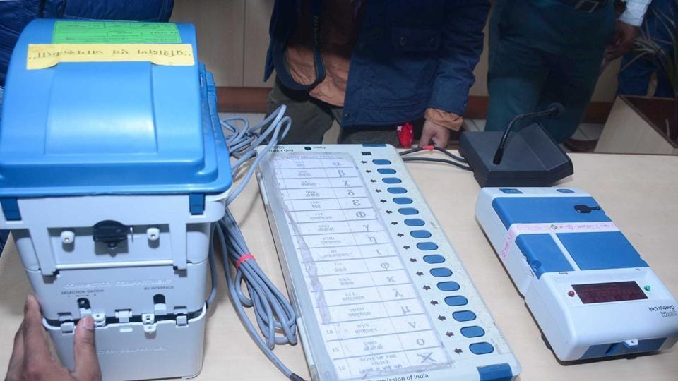 An Electronic Voting Machine (EVM) and Voter verifiable paper audit trail (VVPAT) being checked at a polling station.
