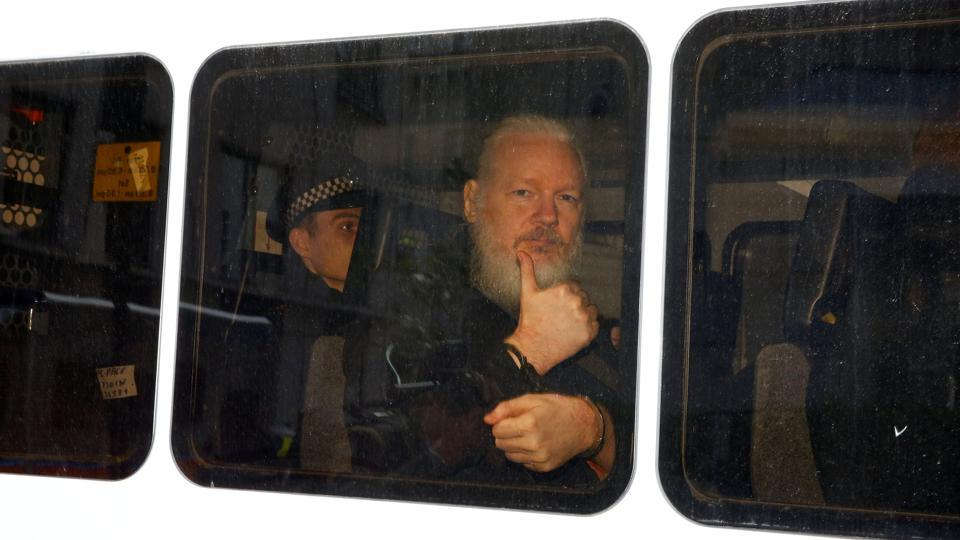 WikiLeaks founder Julian Assange is seen in a police van after he was arrested by British police outside the Ecuadorian embassy in London, England. (Henry Nicholls / REUTERS)