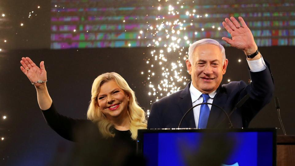 Israeli Prime Minister Benjamin Netanyahu and his wife Sara wave as Netanyahu speaks following the announcement of exit polls in Israel's parliamentary election at the party headquarters in Tel Aviv, Israel. Netanyahu won a tightly contested election cementing a record fifth term in office. (Ammar Awad / REUTERS)