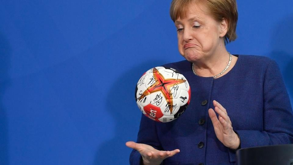 German Chancellor Angela Merkel plays with a handball given to her by the German Handball Federations president (not in picture) as she received the German national handball team at the Chancellery in Berlin, Germany. (John MacDougall / AFP)