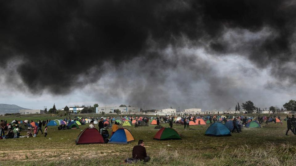 A migrant sits on the grass as smoke from a fire billows above tents outside of a refugee camp in Diavata, a western suburb of Thessaloniki, where migrants gathered in Greece. Hundreds of migrants and refugees gathered following anonymous social media calls to walk until the Northern borders of Greece to pass to Europe. (Sakis Mitrolidis / AFP)