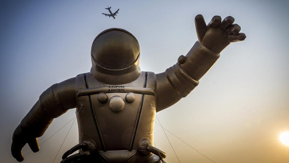 A airliner flies high above a giant gold-colored inflatable astronaut representing Dutch astronaut Andre Kuiper in his astronaut gear to mark the start of the fifth National Museum Week in Sassenheim, Netherlands. (Lex van Lieshout / ANP / AFP)