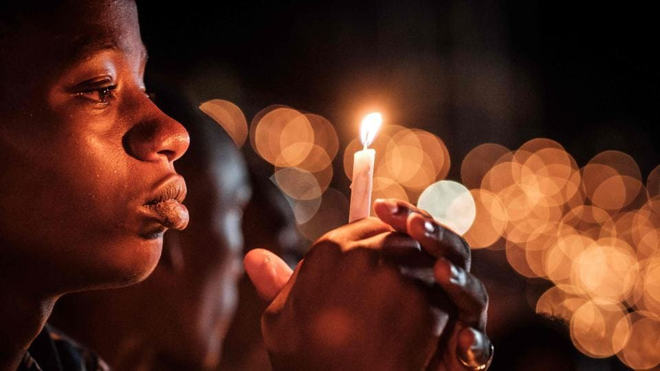 A person holds a candle during a night vigil and prayer at the Amahoro Stadium as part of the 25th Commemoration of the 1994 Genocide, in Kigali, Rwanda. (Yasuyoshi Chiba / AFP)