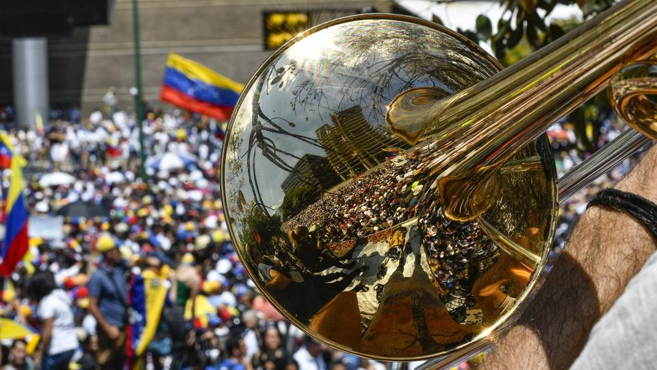 Supporters of Venezuelan opposition leader and self-proclaimed interim president Juan Guaido are reflected on a trumpet during a demo in Caracas, Venezuela. (Matias Delacroix / AFP)