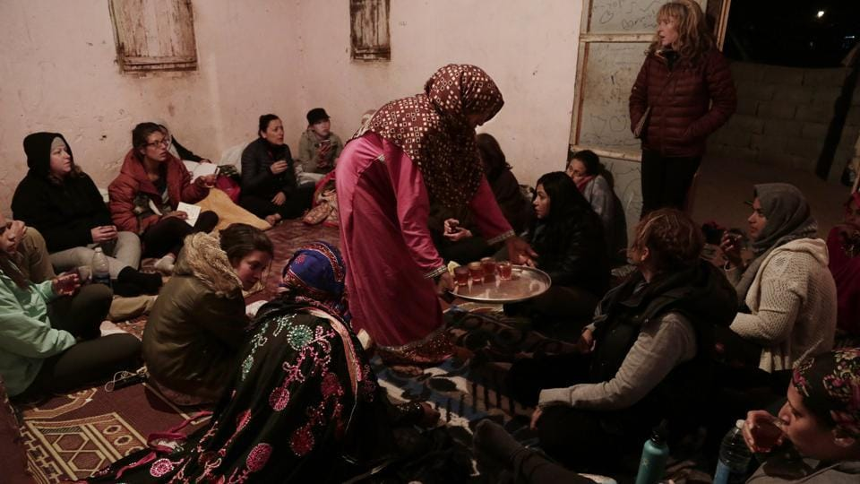Umm Yasser offers tea during a women's only circle of tourists and Bedouin from the Hamada tribe. In the evening, the group returned to the Hamada tribe's village. The women sat on the floor of Umm Yasser's home and the tourists asked the guide about life in the village, marriage and divorce. (Nariman El-Mofty / AP)