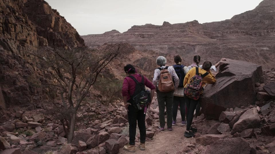 The tourists can only be women, and the tours can't go overnight. Each day before the sun sets, the group returns to the Hamada's home village in Wadi Sahu, a narrow desert valley. The organizers also urge the tourists to photograph the guides only when they are wearing a full veil over the face that covers even the eyes with mesh. Umm Yasser was the first to join. (Nariman El-Mofty / AP)