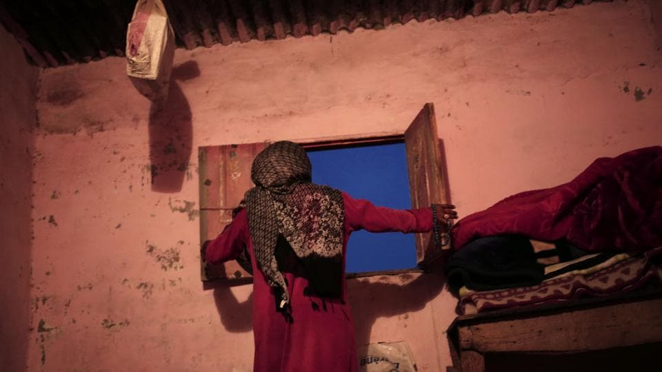 "Umm Yasser at the windows of her home. Some attitudes are changing. Mohammed Salman, an elderly man from the Aligat tribe, said he thought the guides project was a great step for women. ""If a woman wants to work, she should be able to have the right to,"" he said. ""Many men say no, a woman's place is at home. But I'm sick of this ideology. She's a human being."" (Nariman El-Mofty / AP)"