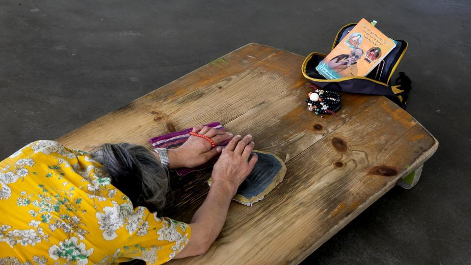 An exile Tibetan woman prays as she prostrates in front of a portrait of Buddhist spiritual leader the Dalai Lama in Dharmsala, Himachal Pradesh. The Dalai Lama was hospitalised briefly in Delhi with chest infection. (Ashwini Bhatia / AP)