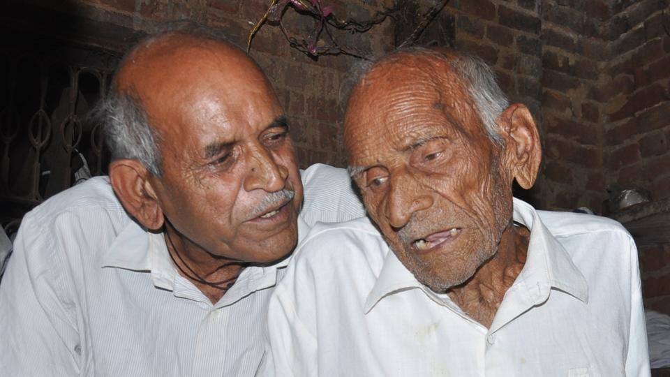 Former village head Ram Prasad Sharma (right) with his son Satish Sharma at his house in Semra village
