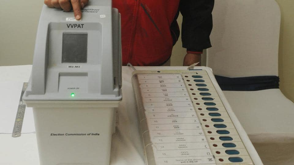 An electoral officer demonstrates  an Electronic Voting Machine (EVM) and Voter Verifiable Paper Audit Trail (VVPAT).