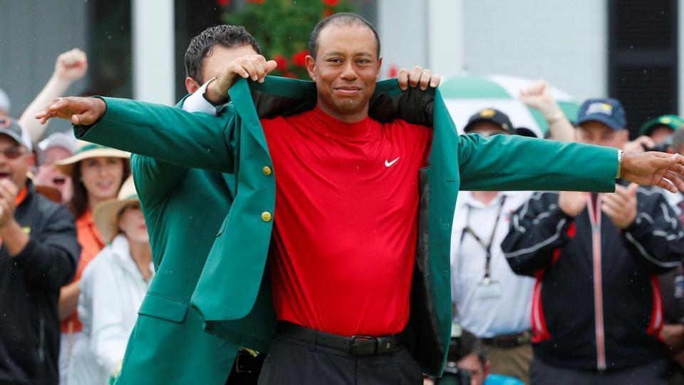 Patrick Reed places the green jacket on Tiger Woods of the U.S. after Woods won the 2019 Masters.