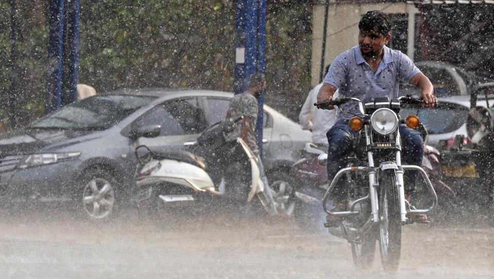 A man rides two-wheeler during sudden rain at Karvenagar on Monday.