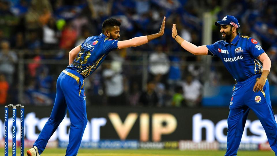 Mumbai Indians cricketer Hardik Pandya (R) and captain Rohit Sharma (L) celebrate after the dismissal of Royal Challengers Bangalore cricketer Parthiv Patel during the 2019 Indian Premier League (IPL)