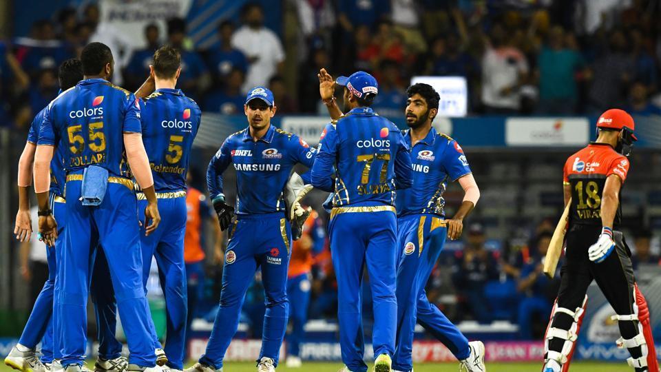 Mumbai Indians cricketers celebrate after the dismissal of Royal Challengers Bangalore captain Virat Kohli (R) during the 2019 Indian Premier League (IPL) Twenty20 cricket match between Mumbai Indians and Royal Challengers Bangalore