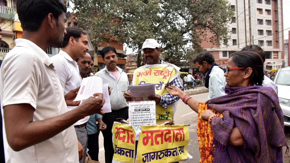"""Lal Mani Das, hands out voting information pamphlets and speaks to prospective voters during his own election awareness campaign in Patna, Bihar. """"I felt a strong urge to do something about how people waste their votes by either electing wrong candidates or not voting at all,"""" Das told AFP as he cycled along a chaotic road with banners festooning his bike and body. (Sachin Kumar / AFP)"""